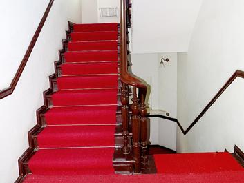 Treppe mit Holzgeländer und Stuckverzierungen